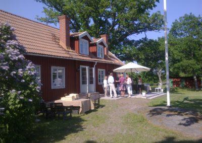 Människor samtalar under parasoll på lilla varandan, på baksidan av Elfsala Gästgård