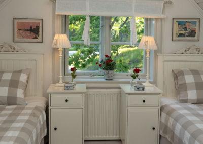 Sovrum med två enkelsängar med fönster mellan på Elfsala Gästgård